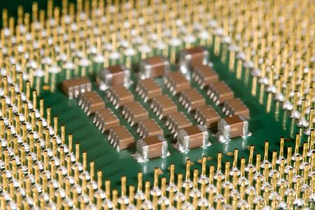 Microchips on the underside of a microprocessor, surrounded by the connector pins like a fence