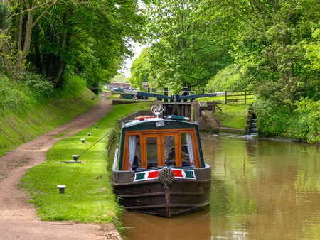 Moored narrowboat between two canal locks  on the Shropshire Union Canal near Audlem in Cheshire, England. Archivio Fotografico