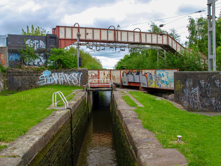 Stoke-on-Trent, Staffordshire, UK - MAY 17, 2015: Footbridge over a railwaybridge over a canal lock on the Trent and Mersey Canal. The walls of the bridges are decorated with graffiti.