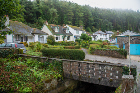 Old stone bridge with white cottages in the picturesque fishing village Polperro in south Cornwall, England. Picture taken from a public street. Editorial