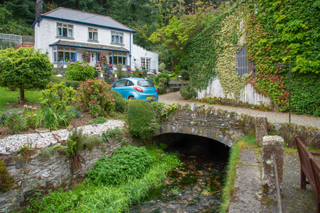 Old stone bridge with a white cottage in the picturesque fishing village Polperro in south Cornwall, England. Picture taken from a public street. Editorial