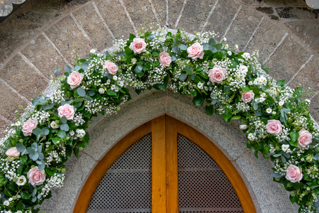 Flower decorated entrance of St. Enodoc Church in Cornwall
