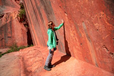 Winzendorf,AUSTRIA - September 21, 2019: Female hiker touches a wall of red marble in an abandoned quarry in the eastern alps. 版權商用圖片 - 142237186