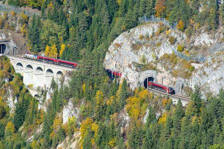 Semmering, AUSTRIA - October 13, 2019: Red train on a viaduct on the Semmering Railway. The Semmering Railway is the oldest mountain railway of Europe and a UNESCO World Heritage site. 版權商用圖片 - 144178603