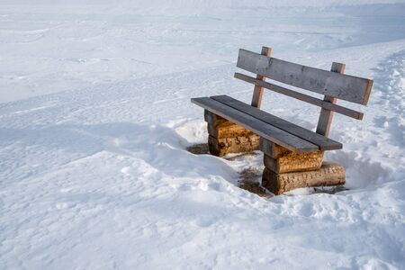 Wooden bench next to a winter hiking trail in the austrian alps in Lungau, Salzburg, Austria. 版權商用圖片 - 138113634