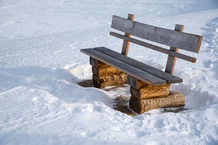 Wooden bench next to a winter hiking trail in the austrian alps in Lungau, Salzburg, Austria. 版權商用圖片