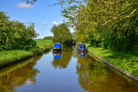 Scenic canal view with approaching narrowboat on the Llangollen Canal near Whitchurch, Shropshire, UK