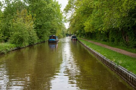 Scenic canal view with approaching narrowboat on the Llangollen Canal near Whitchurch, Shropshire, UK 版權商用圖片