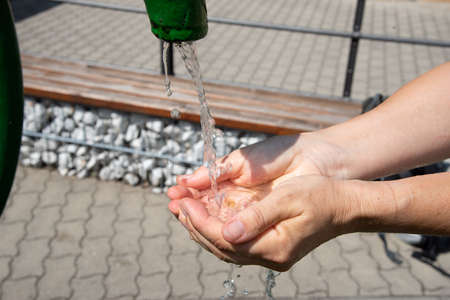 Drinking water from the Kaiserbrunnen (meaning Emperors well) pouring into open palm. The Kaiserbrunnen is one of the wells for the first Vienna Mountain Spring Pipeline and is a major part of Vienna's water supply.
