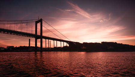staging:  A bridge over dark waters in a reddish purple night setting