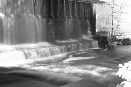 ironworks: Water falling down the exterior of an ironworks building into a stream  Stock Photo