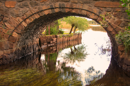 wrack: The passage of a small river full of seaweed, under the arch of a little brickstone bridge  Stock Photo