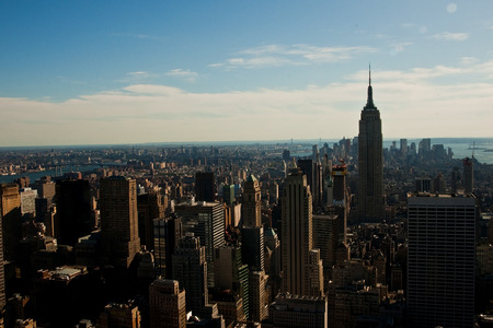 A cityscape picture of New York City in the morning, displaying the ocean in the  photo