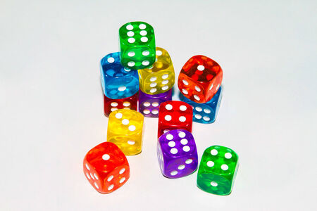 heap of role: A sudio shot of twelve dice of various colors against a white background