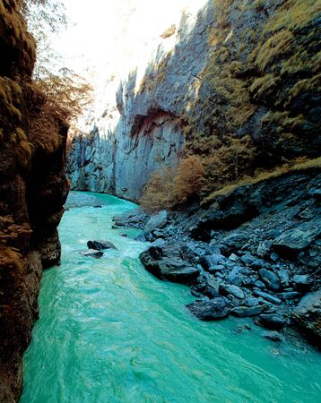 A picture of a clear teal river flowing between the mountain walls of a canyon