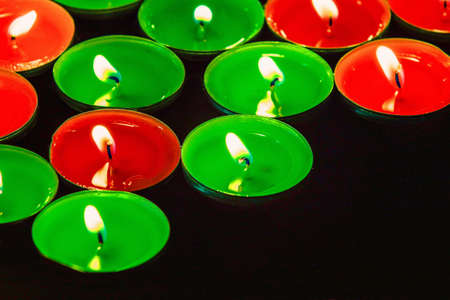 A picture of red and green tealight candles floating on some water in a bowl  photo