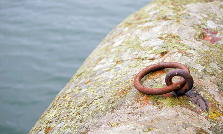 A picture of an old, rusted cast iron anchoring point in a rock by the water photo