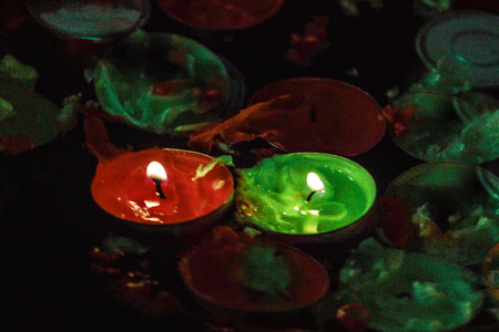tealight: A closeup picture of a few red and green tealight candles floating in a bowl of water, being extinguished by that same surrounding water