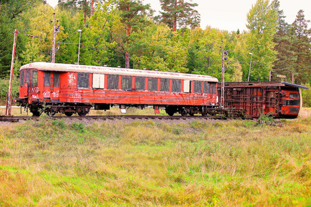 A picture of two rusty, old, abandoned train cars in a lush green landscape, one being toppled over on the track  photo