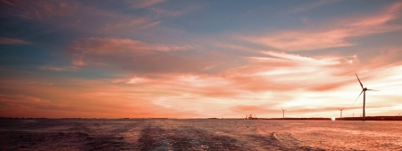 A panoramic landscape picture of wind turbines in the sea under a purple, violet and vivid sky