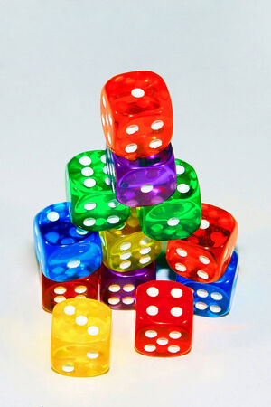 heap of role: A studio shot of twelve six-sided dice of various colors stacked on each other, against a white background