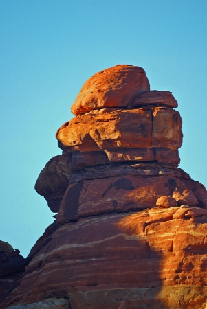 A picture of an orange rock against a light blue, clear sky