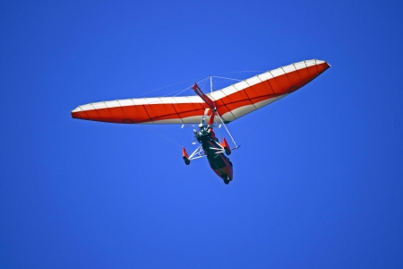 airplane ultralight: A picture of an air trike seen from the behind, in flight against the blue sky  Stock Photo
