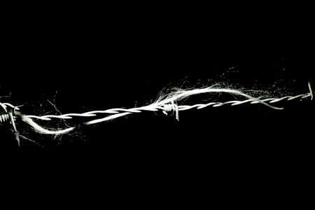 hindering: Detail of a piece of string entangled along some barbwire  Stock Photo