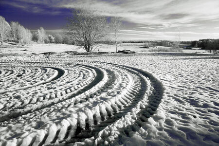 A picture of some tire tracks forming a pattern in the snow of a winter landscape  photo