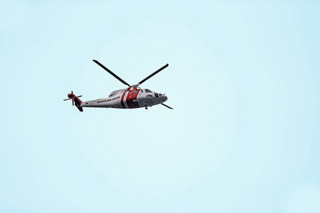 A picture of a rescue helicopter in the light blue sky  photo
