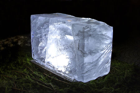 pinetree: A picture of a shining ice block on a bed of fir sticks