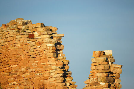 Detail of an old ruined brick wall against a blue sky background  photo