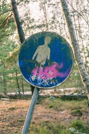 Walk way sign, worn and with graffitti on it