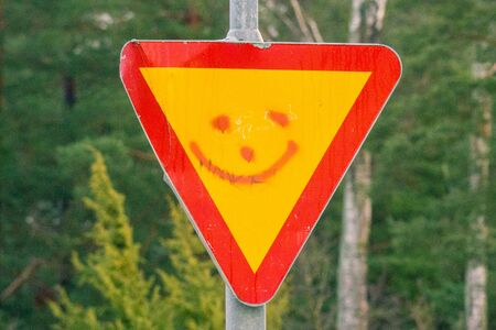 Smiley on a sign for Give priority to traffic on the main road ahead