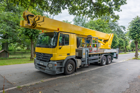 Oslo, Norway - July 21, 2017: A yellow Mercedes-Benz ACTROS 2632 6X4 W/2005 Wumag Wt530 53M with has an articulated boom parked on small road