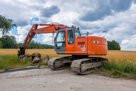 sand quarry: Katrineholm, Sweden -  July  22, 2017: Orange  Excavator  parked by the road partly in a field