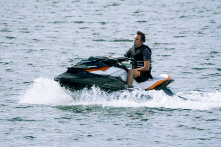 gti: Vastervik, Sweden- July 31, 2017: A man on a  personal watercraft (PWC) a  black, white and orange Sea-Doo GTI 155 in Vastervik harbour