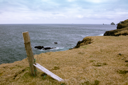 Broken fence posts by the steap cliffs to the sea on Heimaey island in the Vestmannaeyjar archipelago