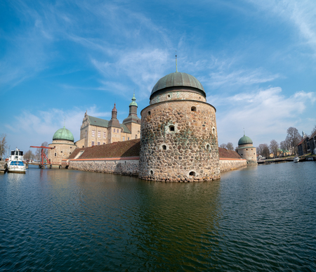 Vadstena, Sweden - April 6, 2019: Vadstena Castle  built in 1545, with a boat ancored to the left in the moat
