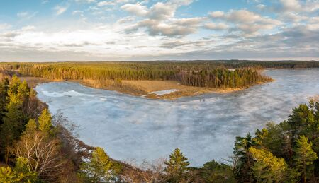 Landscape of a frozen lake in a forested area