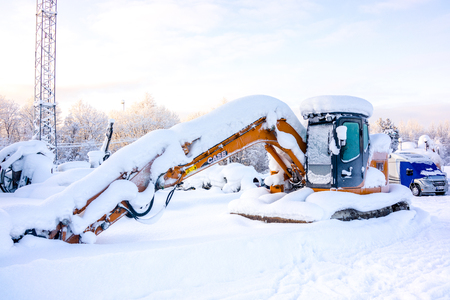 Kiruna, Sweden - February 3 2018: Parked excavator with heavy snow on top 報道画像