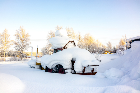 Kiruna, Sweden - February 3 2018: Parked tractor with heavy snow on top