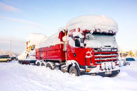Kiruna, Sweden - February 3 2018: Parked red truck with heavy snow on top