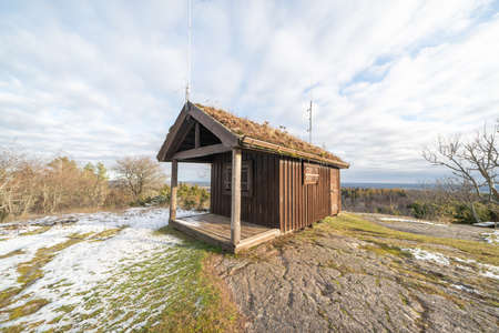 Odeshog, Sweden_November 6, 2019: Small brown cabin with radio masts and grass roof