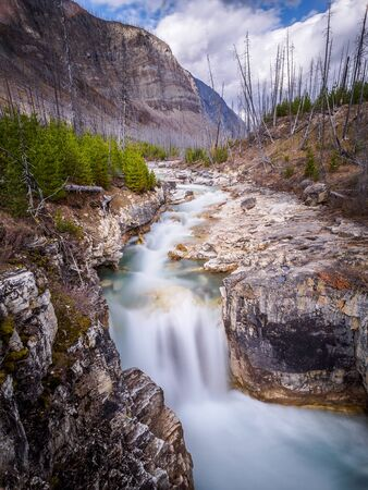 Water flowing over the rough rocks of Marble Canyon, Canada