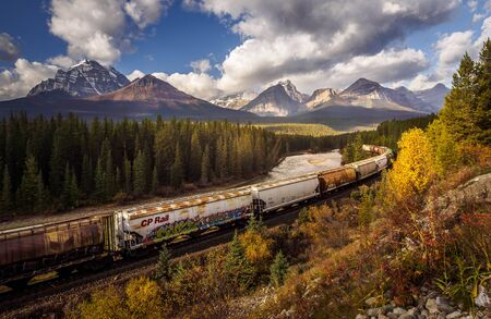 Freight train with many wagon driving in the scenic lanscape of Alberta, Canada 에디토리얼