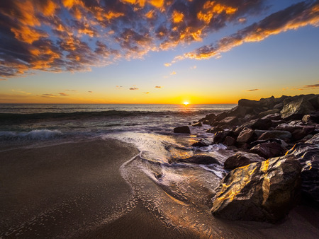 Amazing sunset at the beach reflecting the last sunrays in Namibia 免版税图像