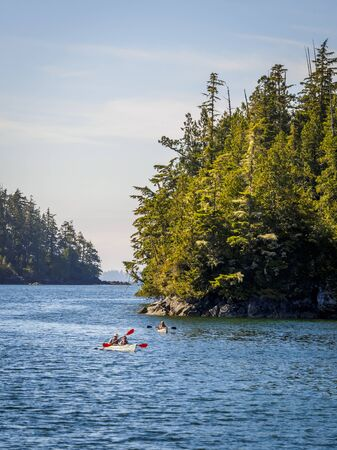 People canoeing through the pacific ocean on the amazing coast of Vancouver Island, Canada