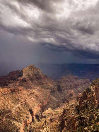 The sun shining through the big heavy clouds during a thunderstorm over the Grand Canyon North Rim