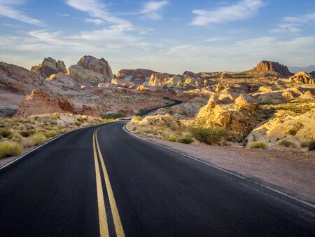 Black road leading into the colorful mountains of Valley of Fire State Park, Nevada